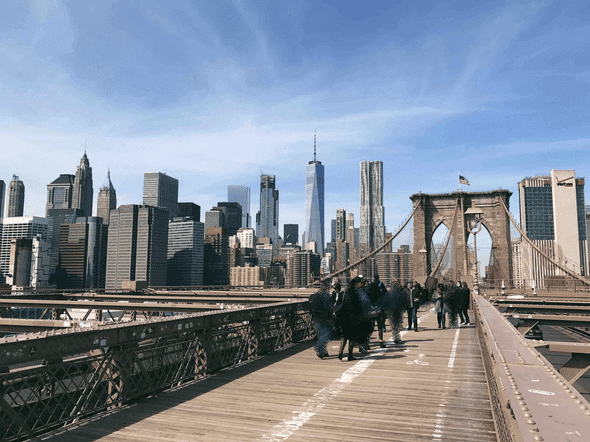 The image of Brooklyn Bridge with some pedestrians fuzzed out